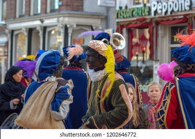 Gouda, The Netherlands - November 18, 2006: so-called black Petes having a conversation during the yearly parade of Saint Nicholas. Two little girls are looking at them.