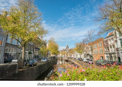 Gouda, The Netherlands - October 15th 2018. Traditional dutch canal houses of Gouda with trees in autumn colors.
