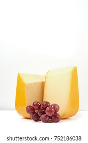 Gouda sliced cheese with fresh grape. White background with empty space.