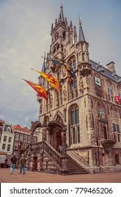 Gouda, southern Netherlands - June 29, 2017. People at gothic City Hall and flags on cloudy day ain Gouda. Very popular day trip destination, is famous for its Gouda cheese. Retro vintage filter