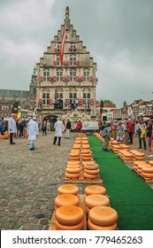 Gouda, southern Netherlands - June 29, 2017. Stacks of cheeses for sale at the Market Square fair and gothic City Hall in Gouda. Very popular day trip destination, is famous for its tasty Gouda cheese
