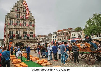Gouda, southern Netherlands - June 29, 2017. People carrying cart with cheese at the end of Market Square fair in Gouda. Very popular day trip destination, is famous for its tasty Gouda cheese.