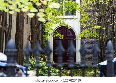 Gouda, South-Holland/The Netherlands - October 27 2018: Picture of an old house in Gouda city center shot through the front gate out of focus and the garden and entrance in focus