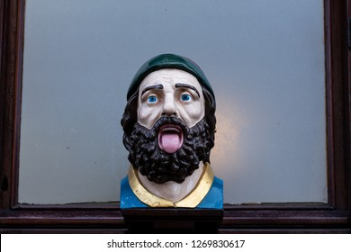 Gouda, South-Holland/The Netherlands - October 27 2018: Close up of wooden bust above a barbershop in the city of Gouda looking like a jawning man