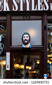 Gouda, South-Holland/The Netherlands - October 27 2018: Part of the entrance with wooden bust from a barbershop in the city of Gouda looking like a jawning man