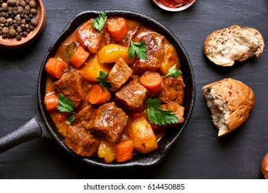 Goulash, beef stew in cast iron pan on dark background, top view, close up
