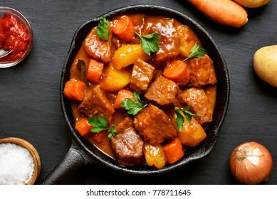 Goulash, beef stew in cast iron pan. Top view, flat lay food