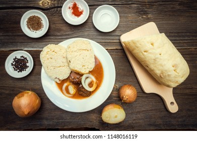 Goulash with Dumplings and Raw Cooking Ingredients on Wooden Background. Czech Republic Homemade Cuisine.