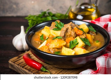 Goulash with meat and vegetables in black bowl. Beef stew with vegetables. European cuisine.