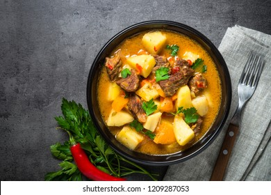 Goulash with meat and vegetables on black background. Beef stew with vegetables. European cuisine. Top view with copy space.