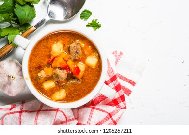 Goulash soup with meat and vegetables on white stone table. European cuisine. Top view with copy space.