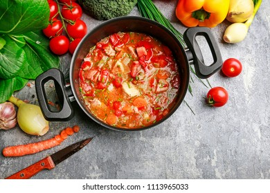 Goulash soup, salmon fillet and colorful vegetables on grey stone background.