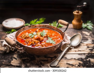Goulash or stew in copper pan with spoon on rustic kitchen table over dark wooden background