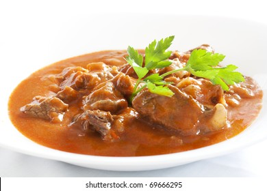 Goulash stew with parsley served in white bowl
