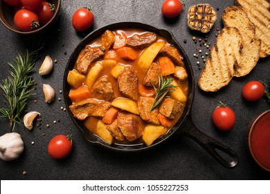 Goulash stewed meat with potatoes, carrots and vegetables in a cast-iron frying pan on a wooden background with croutons, rosemary, garlic and tomatoes. Close up. Flat lay. Top view.