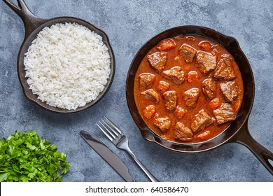 Goulash traditional homemade European beef meat stew soup food cooked with spicy gravy sauce in cast iron skillet meal served with rice and parsley on blue concrete kitchen table background.
