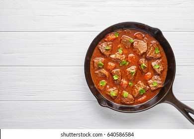 Goulash traditional homemade Hungarian beef meat stew soup food with spicy gravy in cast iron pan skillet meal with paprika on white wooden kitchen table background.