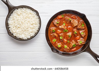 Goulash traditional Hungarian beef meat stew soup food cooked recipe with spicy gravy sauce in cast iron pan meal served with rice and chopped parsley on white wooden texture kitchen table background.