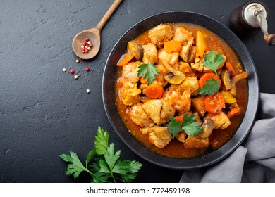 Goulash traditional Hungarian dish. Stew with pepper and tomato sauce in ceramic plate on dark black stone or concrete background. Selective focus. Top view.