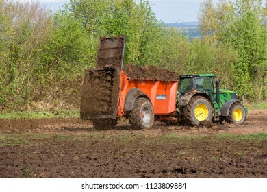 GOULT, NORMANDY, FRANCE - April 23, 2018: A farmer using a manure spreader behind his tractor to spread an organic mixture of manure and hay on his land for fertilisation.