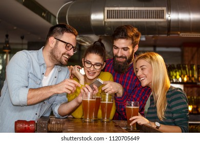 Goup of four friend in local pub looking at mobile phone and smile with glass of beer on hands