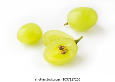 Goup of grape berries, one cuted in half on white background, view from above