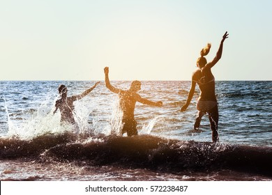 Goup of three friends having fun or dancing at beach party at sunset time. Space for text
