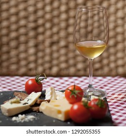 Gourmet: assortment of delicious french cheese served on black choalk board with fresh tomatoes. Glass of cold white wine. Decoration with plaid red and white tablecloth