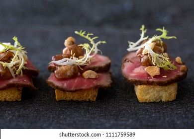 Gourmet beef filet canapes with tofu crumble, chicken bites & risee garnish on toast