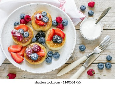 Gourmet Breakfast - Cottage cheese pancakes, syrniki, curd fritters with raspberry, strawberry, blueberry, BlackBerry and powdered sugar in a white plate.   Selective focus