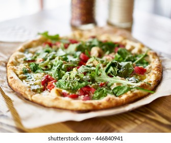 gourmet brick oven fired chicken and pesto pizza in restaurant shot with selective focus