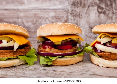 Gourmet burgers on wooden plate. Fast food. Unhealthy snack
