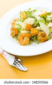 Gourmet caesar salad with grilled shrimp and croutons.