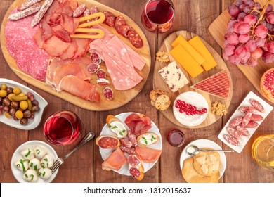 Gourmet Charcuterie. An assortment of sausages and hams, deli meats, and a cheese platter, shot from the top on a dark rustic background with wine and olives