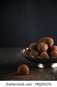 Gourmet cocolate truffles on a dark mood and background.