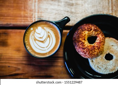 Gourmet coffee with asiago bagel on a plate with wooden table background.