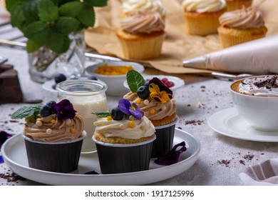 Gourmet cupcakes, cappuccino and chocolate chips. Cupcakes covered with edible flowers. A large piece of chocolate, raw cupcakes, a cup of coffee with cream and creamy, cappuccino. Dessert design