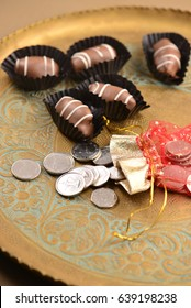 Gourmet date chocolates arranged with a pouch of UAE Dirham coins.