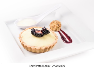 Gourmet Dessert. Cream-tart with black berry and berry coulis sauce