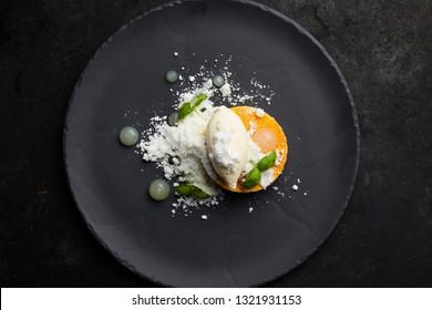 Gourmet dessert made of mango, vanilla ice craeam , coconut powder and lychee sauce