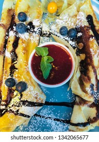 Gourmet dish in the restaurant: pancakes with berries, chocolate and lingonberry sauce
