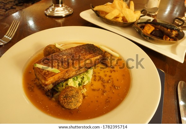 Gourmet dish - roasted pork belly, grilled vegetables and French fries
