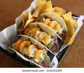 Gourmet fish tacos decorated with mandarin orange slices and a side of tortilla chips
