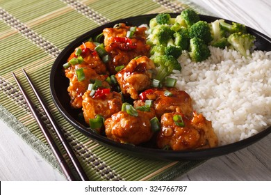 Gourmet Food: chicken general Tso's with rice, onions and broccoli close-up on a plate. horizontal