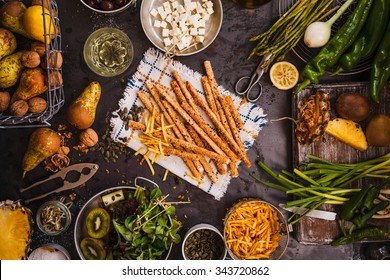 Gourmet food concept. Various Snacks and fruits, veggies table from above. Wholegrain Grissini, feta cheese, fries nuts, tropical fruit sliced, green salad leaves, over dark rustic table.