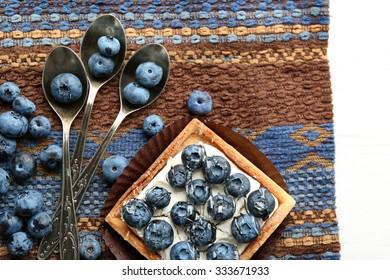 Gourmet fresh blueberry tart on napkin, close up