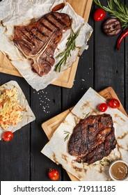 Gourmet Grill Restaurant Steak Menu - T-Bone and Rib Eye Beef Steak on Black Wooden Background. Black Angus Prime Beef Steak. Beef Steak Dinner. Top VIew