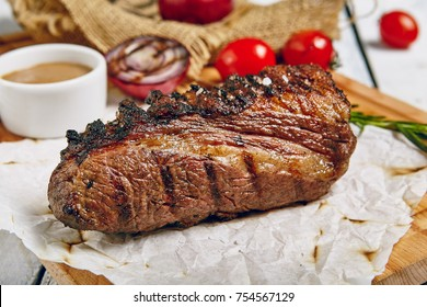 Gourmet Grill Restaurant Steak Menu - Tri-Tip Beef Steak on Wooden Background. Black Angus Prime Beef Steak. Beef Steak Dinner. Top VIew