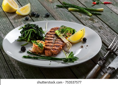 Gourmet grilled salmon fish steak and vegetable salad on a plate. Delicious healthy meal made of fish and vegetables on a rustic table.