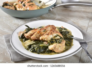 Gourmet homemade chicken florentine with a cast iron skillet in the background
